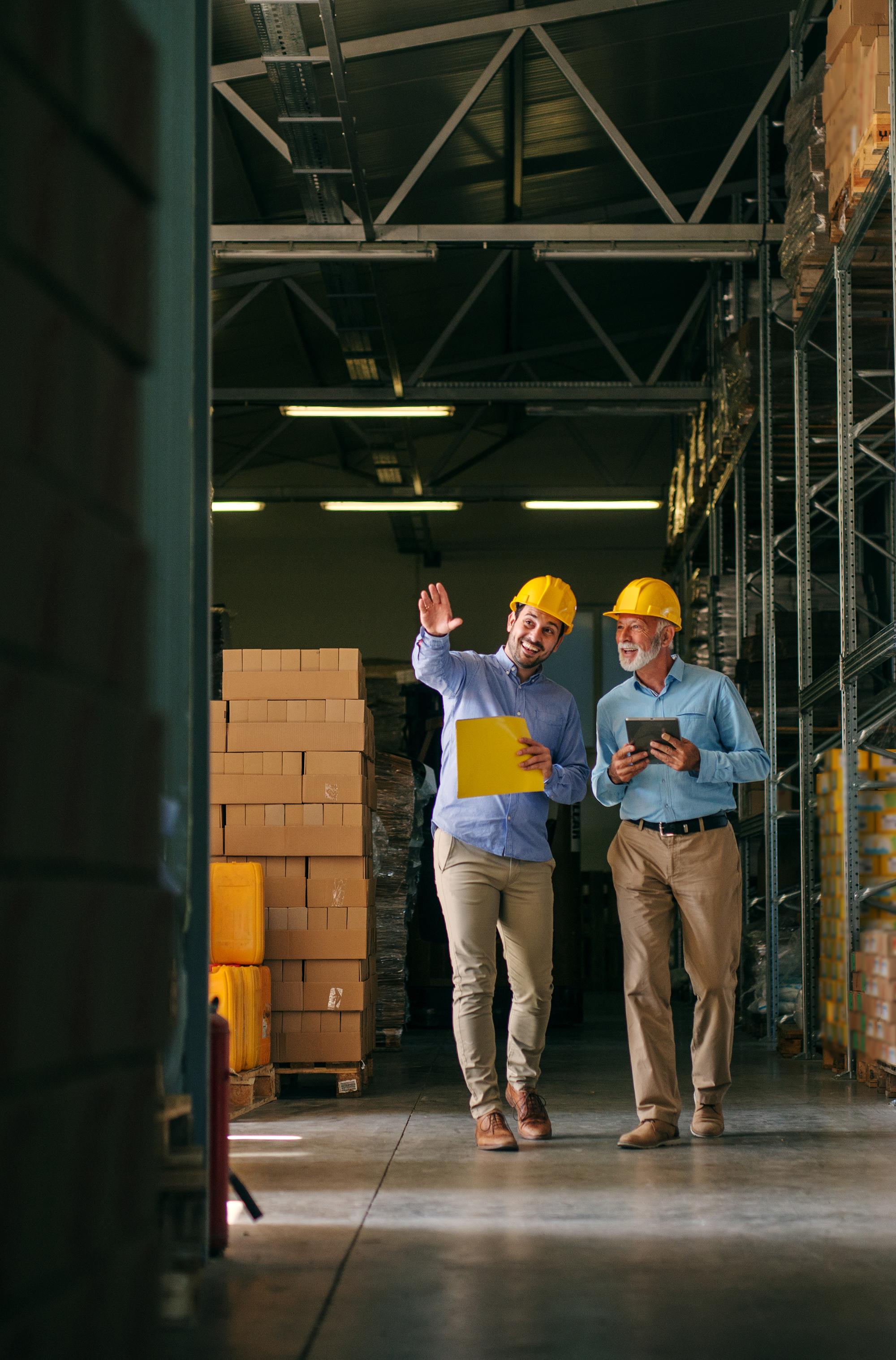 Two men walking through big warehouse