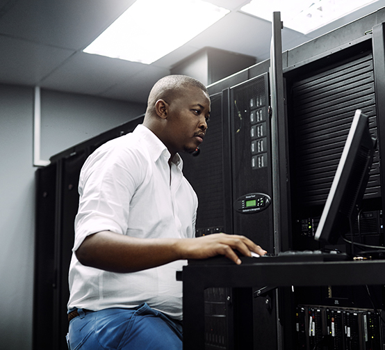 IT technician using a computer while working in the server room