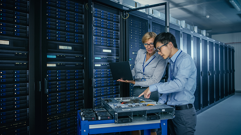 Two people working in a server room
