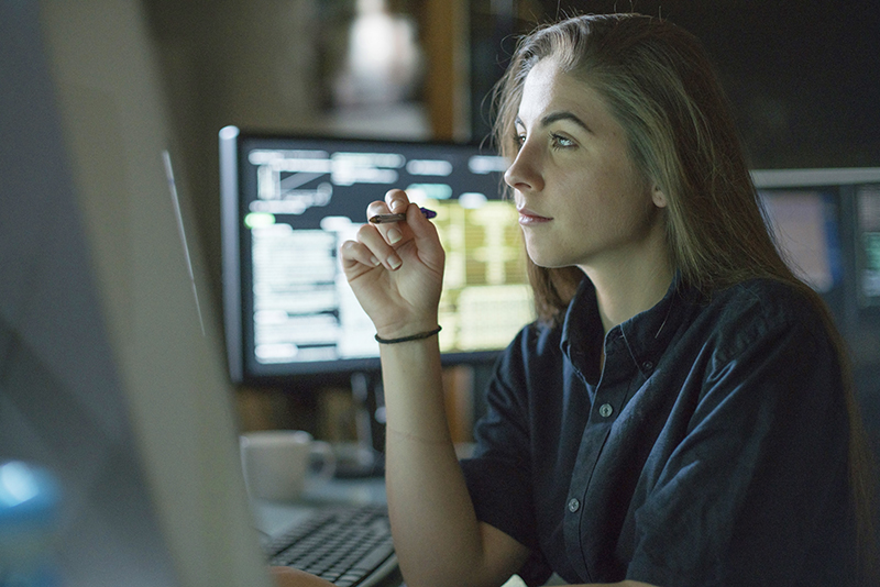A young woman is seated at a desk surrounded by monitors displaying data