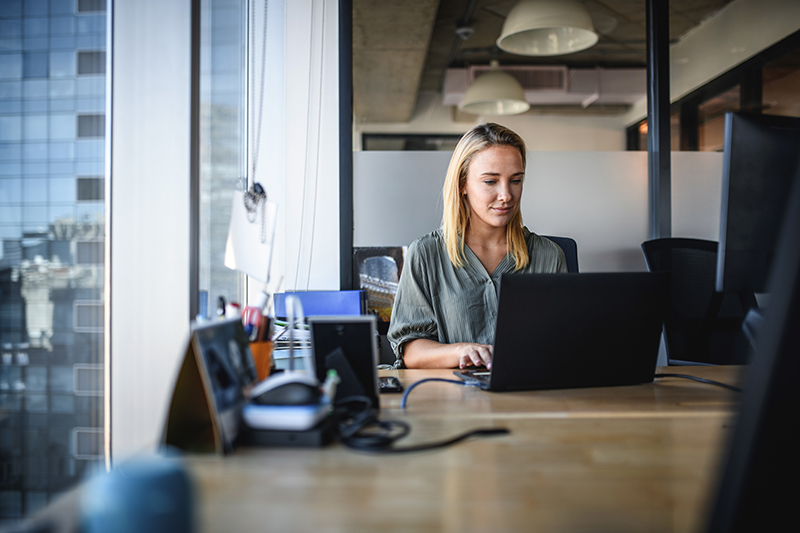 Focused Young Businesswoman Working on Laptop in Office