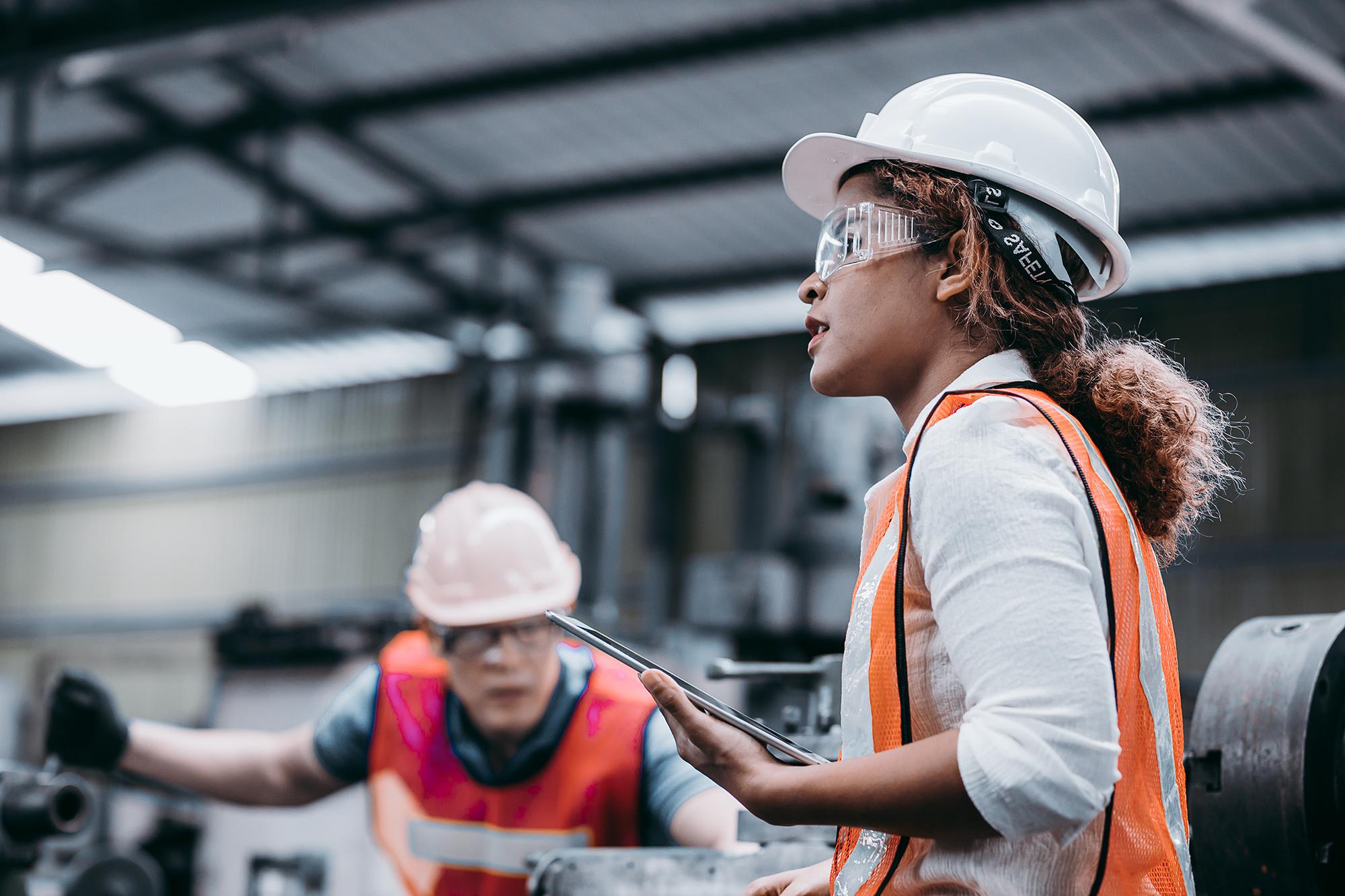 Female industrial engineer wearing a white helmet