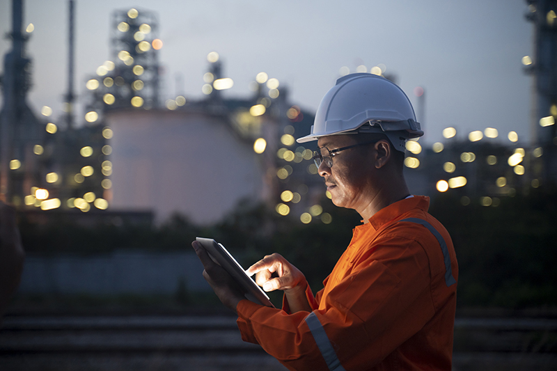 Engineer using tablet near oil refinery at night