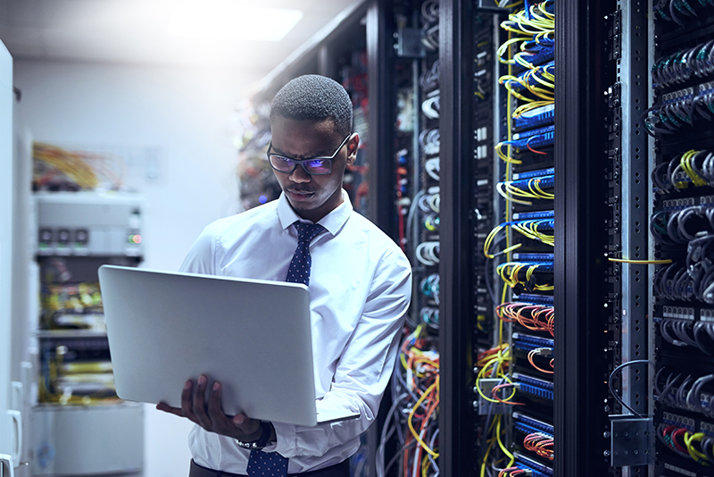 IT technician working on his laptop while standing inside of a server room