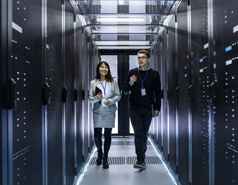 Two people walking through a server room