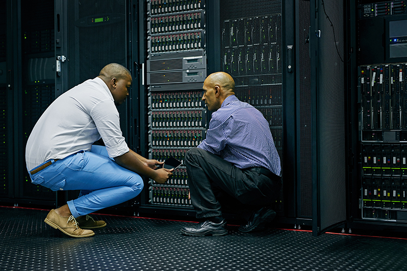 two IT technicians repairing a computer