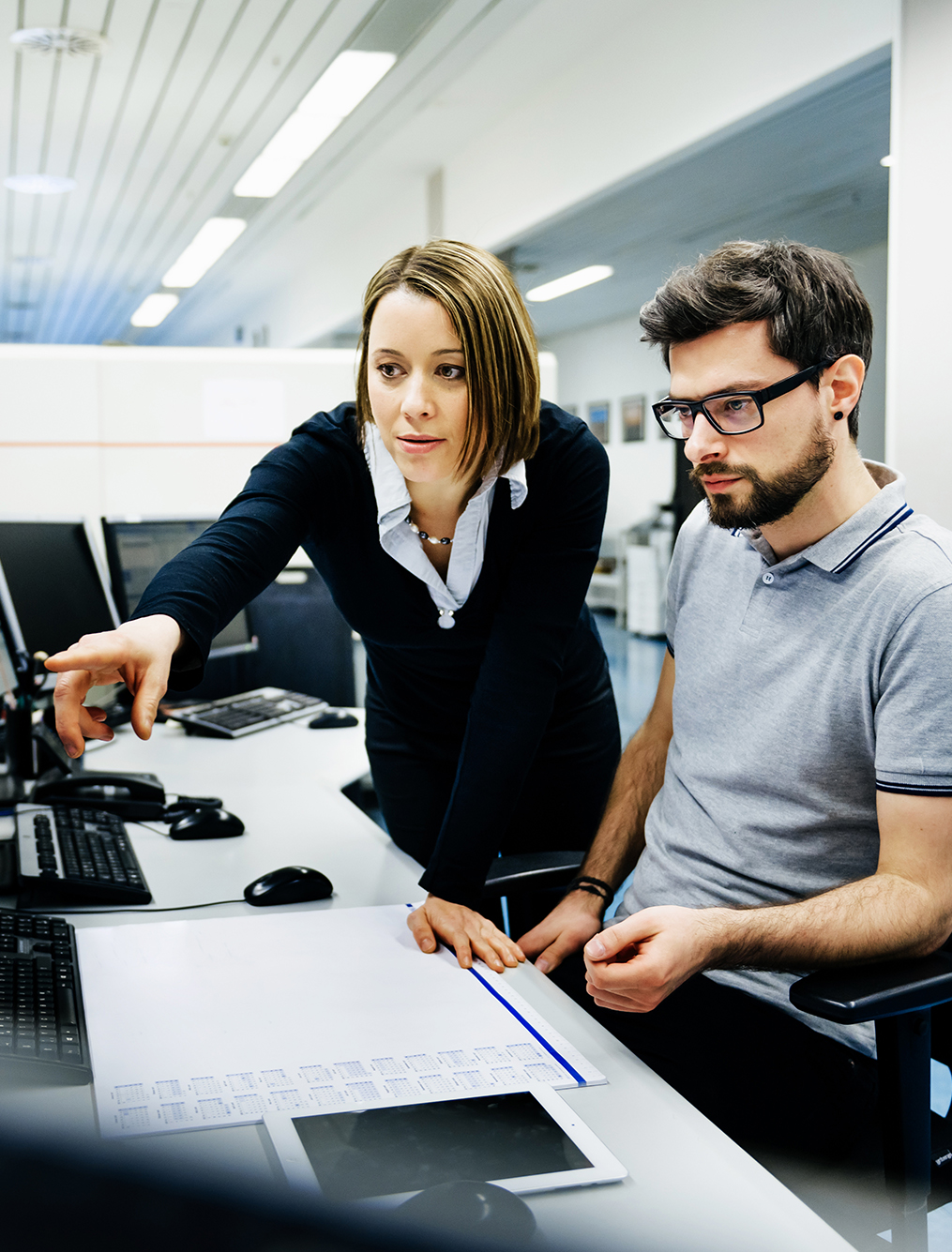 Two IT professionals in a big control room of a factory talking.