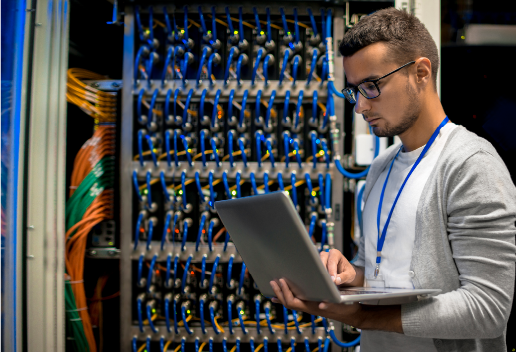 Side view portrait of young man with laptop standing by server cabinet