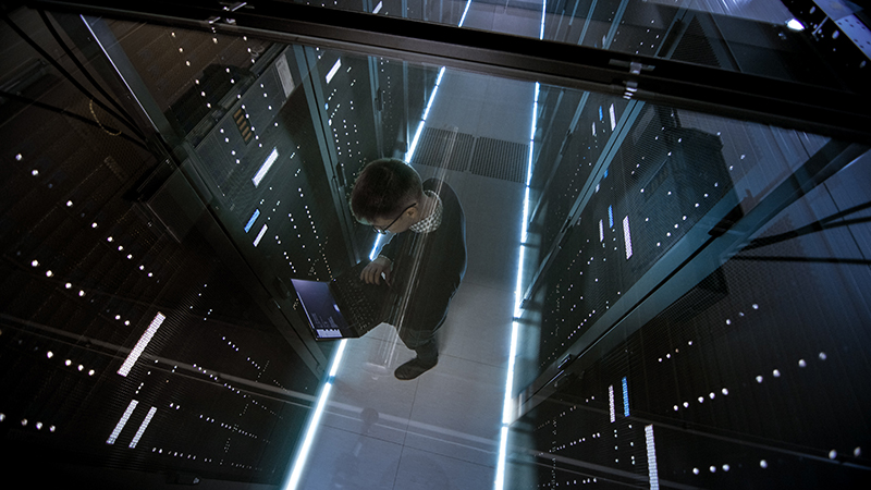 Top View Through the Glass of IT Engineer Working with Laptop