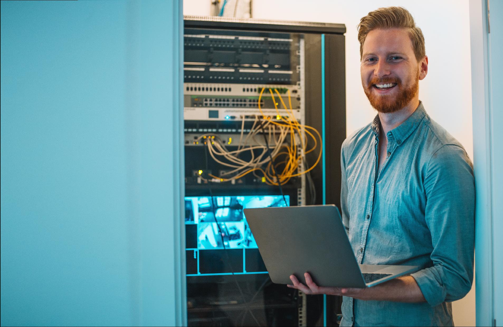 Male IT technician using laptop in server room