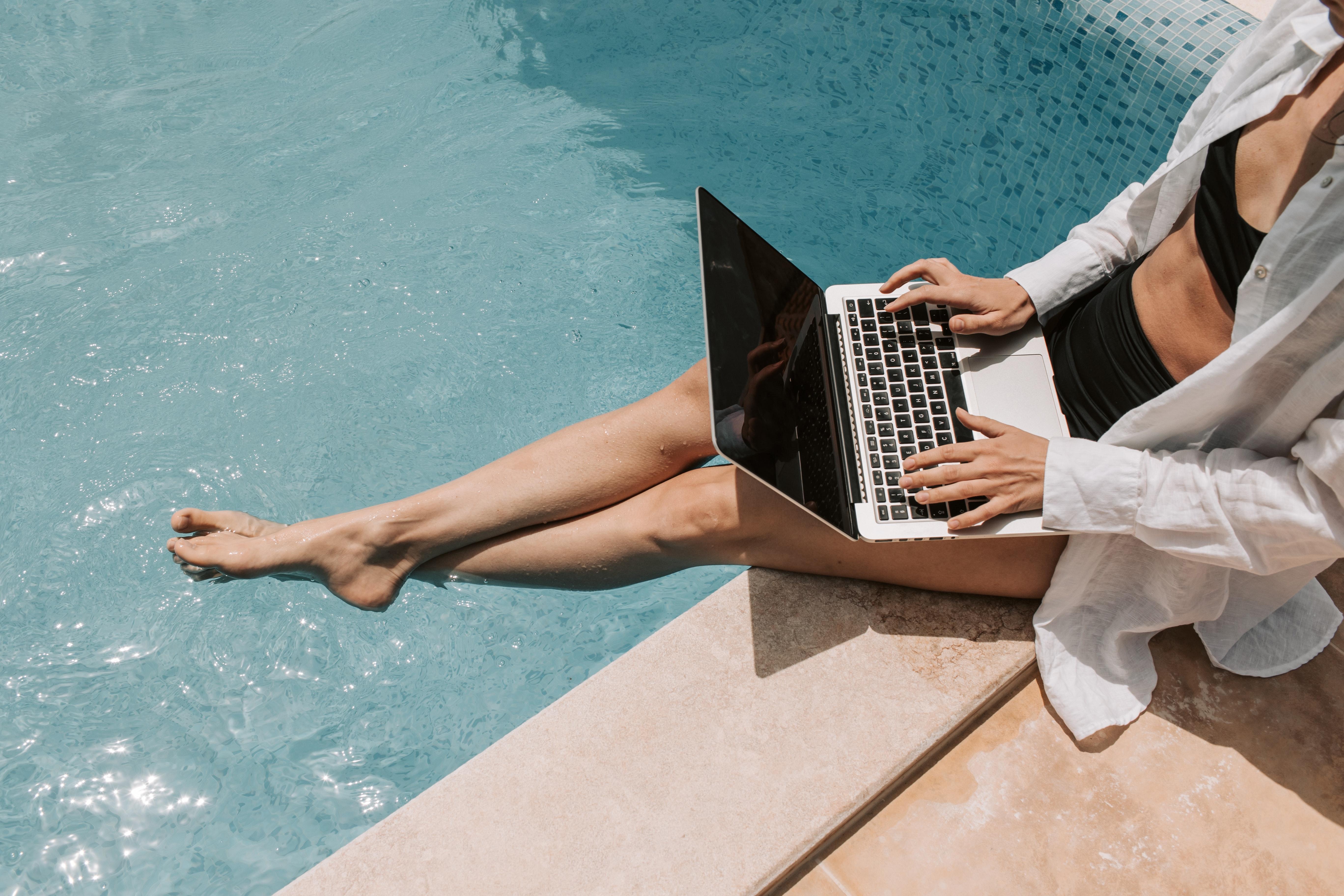 Women sitting poolside working on her laptop